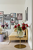 Glass vase of red peonies, sofa and gallery of photographs on wall of living room