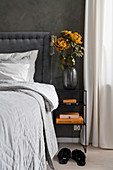 Double bed with headboard and bedside table in bedroom with dark grey wall