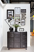 Chest of drawers on castors below arrangement of pictures and ornaments on wall