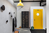 Industrial-style chest of drawers and yellow door in loft apartment