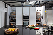 Island counter with black, high-gloss worksurface in open-plan kitchen