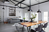 Rustic dining table, grey sofa and child's swing in loft apartment