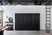 Black serving trolley next to black, industrial-style cupboard