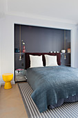 Double bed with head in grey-painted niche in bedroom