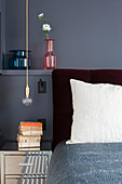 Bedside table and pendant lamp next to double bed with head in grey-painted niche