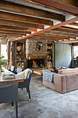 Rustic living room with concrete floor and wooden ceiling beams