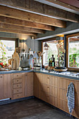Modern country-house kitchen with wooden cupboards and wood-beamed ceiling