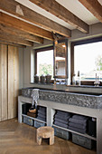 Stone trough used as sink in rustic bathroom with wood-beamed ceiling