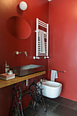 Sewing machine table used as washstand in bathroom with red walls