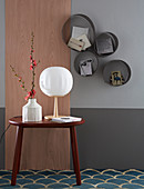 Wooden panel and side table next to round shelf modules on two-tone wall