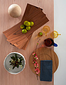 Bowl made from wooden veneer, crockery and decorations on table