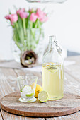 Bottle of lemonade, glass, lemon and lime on wooden board