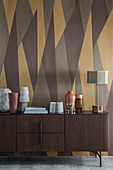 Dark wooden sideboard against wall with brown retro pattern