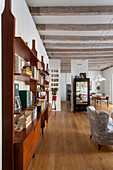 Retro shelved in open-plan interior with wood-beamed ceiling and wooden floor