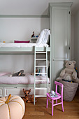 Pink chair next to bunk beds in classic children's bedroom