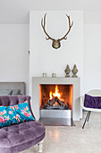 Antlers above fireplace in living room with purple easy chair in foreground