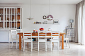 Wooden dining table, white chairs and dresser