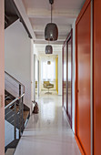 Long corridor with fitted cupboards and staircase