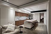 Fitted kitchen, living area and ceiling spotlights in open-plan interior