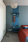 Blue cloakroom panel used as bedside table between bed and wire chair