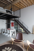 Classic chairs in dining area next to staircase and designer chairs in foreground in loft apartment
