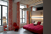 Double bed with red cover, red designer chair and cheval mirror in loft apartment