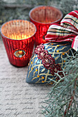 Red tealight holders next to unusual Christmas-tree bauble