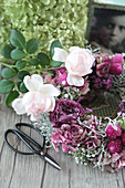 Wreath of dried roses, hydrangeas, silver ragwort and gypsophila decorated with vintage photo and scissors