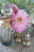 Dahlienblüten als Dekoration mit Bauernsilber und Flasche