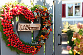Welcome wreath on garden gate made from moss heart with rosehips, rowan berries and pyracantha berries