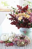 Bouquet of chrysanthemums with autumn leaves, white pumpkins with a wreath of hydrangea flowers and pink pepper, leaves from the sweetgum tree