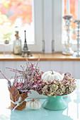 Weiße Kürbisse mit Kranz aus Hortensienblüten und rosa Pfeffer, Knospenheide in Topf mit Ahornblatt