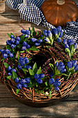 Closed Gentiana with budding heather and twigs tied to a wreath