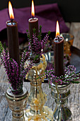 Candlestick with budding heather and burning candles