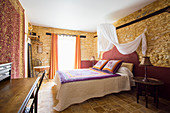 Double bed with canopy in bedroom with stone walls