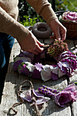 Woman creating wreath of ornamental cabbage leaves and sedum