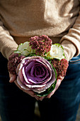 Woman holding bouquet of ornamental cabbages and sedum
