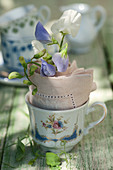 Small cup with sweet peas in a napkin