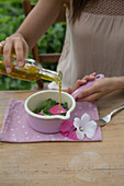 Preparing a mallow poultice: cover mallow leaves and flowers with olive oil