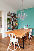 Dining table with solid wooden top next to turquoise wall and shelving