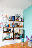 Wall-mounted shelves next to turquoise wall in dining room
