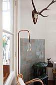 Standard lamp, hunting trophy and log burner in corner