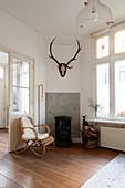 Rattan armchair, standard lamp, hunting trophy and log burner in corner