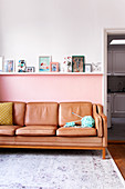 Leather sofa against pink wall below photos and pictures on ledge