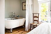 Vintage bathtub behind curtain in bedroom