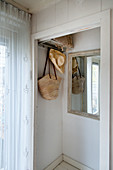 Coat rack and mirror on wall in niche