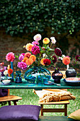 Dahlias in blue glass vase on set table outdoors