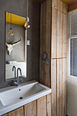 Sink next to rustic fitted cupboard made from reclaimed wooden boards