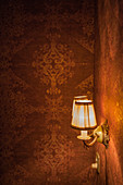 Sconce lamps on wall with Baroque-style wallpaper
