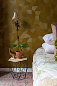 Metal bedside table next to bed in bedroom with patterned wallpaper